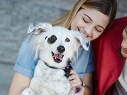 adopter smiling at her small white dog
