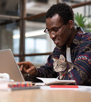 man working on his laptop with his cat in his arms